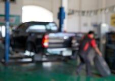 Suddigt av bilteknikeren som reparerar gummihjulet arkivfoto