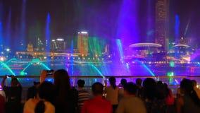 Suddigt folk på förgrundsklockaspektren ljus och vattenshow på händelseplazaen i Singapore stock video