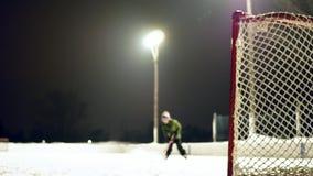 Suddigt gem av den utomhus- isisbanan på natten med pojken som åker skridskor och skjuter pucken arkivfilmer