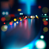 Suddigt tänder på den regniga stadsvägen på natten.