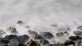 Suddigt vatten över vaggar arkivbild