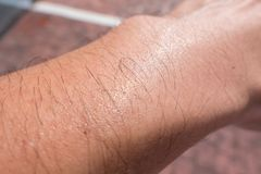 Sude el verano caliente del día del brazo del pelo del poro masculino de la piel imagen de archivo