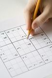 Sudoku. Puzzle and hand holding pencil Stock Images