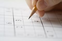 Sudoku. Puzzle and hand holding pencil Royalty Free Stock Photo