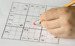 Sudoku. Puzzle and hand erasing, focus on mistake Royalty Free Stock Image