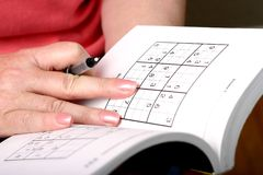 Sudoku. Woman figuring out a sudoku puzzle stock images