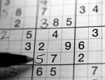 Sudoku in Black and White. Left handed person solving a su doku puzzle Stock Photo