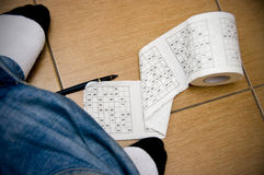 Sudoku boredom in toilet Royalty Free Stock Photo