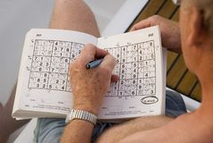 Sudoku on holiday. A game of Sudoku on a sailing holiday in the Mediterranean stock photos