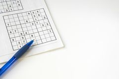 Sudoku non résolu étendu par appartement, stylo bleu, sur la table blanche L'espace pour le texte image stock
