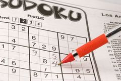 Sudoku puzzle. In newspaper being solved with an orange pen Stock Photography