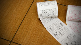 Sudoku toilet paper. Two rolls of toilet paper with sudoku lying on the floor Royalty Free Stock Image