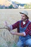 Sudore di giovane agricoltore lavorante con una falce vicino ad un campo bianco Fotografie Stock Libere da Diritti