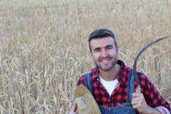 Sudore di giovane agricoltore lavorante con una falce vicino ad un campo bianco Fotografia Stock