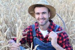 Sudore di giovane agricoltore lavorante con una falce vicino ad un campo bianco Immagini Stock