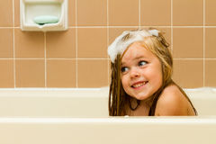 The suds of soap and a smile. Cute photo of a girl smiling with soap suds in her hair while playing in the tub Stock Images