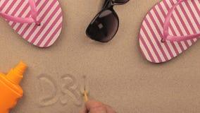 SUEÑA la inscripción escrita a mano en la arena, entre los accesorios de la playa metrajes