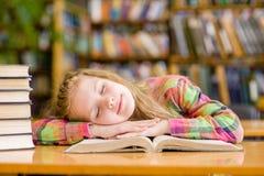 Sueño adolescente de la muchacha en biblioteca Fotos de archivo