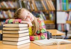 Sueño adolescente de la muchacha en biblioteca imagenes de archivo