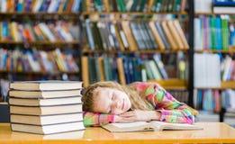 Sueño adolescente de la muchacha en biblioteca Fotos de archivo libres de regalías