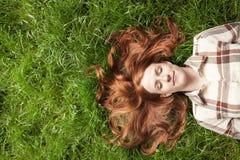 Sueño adolescente en hierba con los ojos cerrados Fotografía de archivo libre de regalías