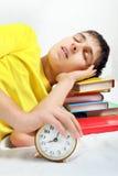Sueño cansado del estudiante con el despertador Foto de archivo libre de regalías