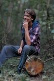 Sueño con un hombre que sienta en un inicio de sesión el bosque imagenes de archivo