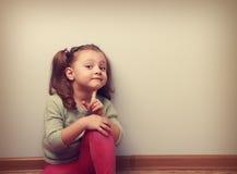 Sueño de la muchacha sonriente del niño que se sienta que mira la diversión con el finger cerca de f imagenes de archivo