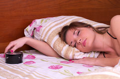 Sueño de la mujer en cama con la alarma Imagen de archivo