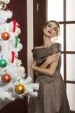 Sueño de la mujer en vestido elegante cerca del árbol de navidad Imagenes de archivo