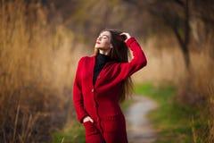 Sueño de la mujer joven Hembra hermosa con el pelo sano largo que disfruta de la naturaleza en el parque que lleva la rebeca roja Fotografía de archivo