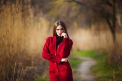 Sueño de la mujer joven Hembra hermosa con el pelo sano largo que disfruta de la naturaleza en el parque que lleva la rebeca roja Foto de archivo libre de regalías