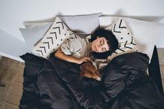 Sueño de la mujer y del perro en cama imagen de archivo libre de regalías