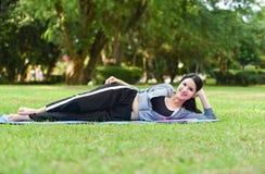 sueño de la postura del ejercicio en la hierba Imagenes de archivo