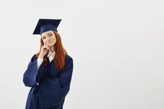 Sueño de pensamiento graduado de la muchacha hermosa soñadora sobre el fondo blanco Copie el espacio Fotografía de archivo