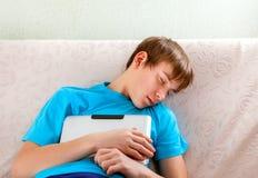 Sueño del adolescente con una tableta Fotos de archivo