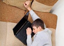 Sueño del adolescente en el ordenador portátil Imagen de archivo libre de regalías