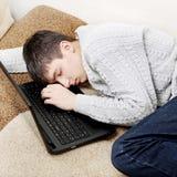 Sueño del hombre joven en el ordenador portátil Imagen de archivo
