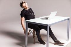 Sueño del hombre joven mientras que lleva los auriculares y el trabajo sobre el ordenador portátil en su tabla de la oficina en e fotos de archivo libres de regalías