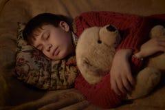 Sueño del muchacho en cama con el juguete del oso imágenes de archivo libres de regalías