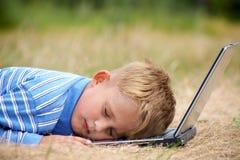 Sueño del muchacho en la computadora portátil Fotos de archivo libres de regalías