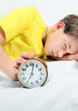 Sueño del niño con el despertador Fotos de archivo libres de regalías