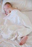 Sueño del niño pequeño en la cama blanca. Fotografía de archivo