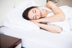 Sueño hermoso de la mujer joven en la cama en casa fotos de archivo libres de regalías