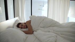 sueño Mujer que duerme en cama con el lecho blanco en el dormitorio ligero almacen de video