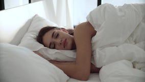 sueño Mujer que duerme en cama con el lecho blanco en el dormitorio ligero almacen de metraje de vídeo