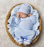 Sueño recién nacido del bebé en la cesta, niño recién nacido que duerme en azul Foto de archivo