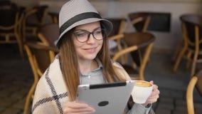 Sueños de la muchacha con la tableta y el café almacen de video