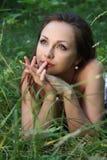 Sueños de la muchacha en hierba. Fotografía de archivo