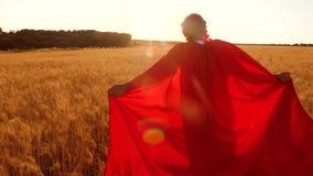 Sueños del niño a volar La muchacha juega al super héroe en impermeable rojo y corre a lo largo de campo amarillo en el cielo azu almacen de video